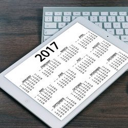 An iPad showing a calendar resting on a keyboard