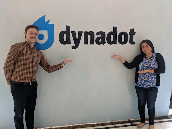 Two people in front of Dynadot logo