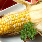 Cooked corn on the cob with a side sprig of parsley