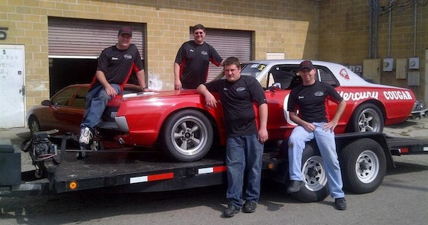 Four men surrounding a red sports car on the bed of a tractor trailer