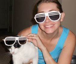 The author Robyn Norgan wearing sunglasses and posing with a cat wearing sunglasses