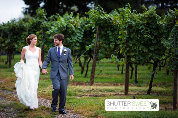 A recently married couple walking through an orchard